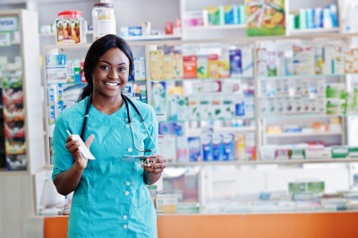 female pharmacist smiling while holding a medication bottle
