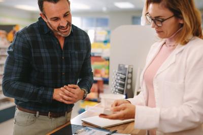 male pharmacist talking to his female customer