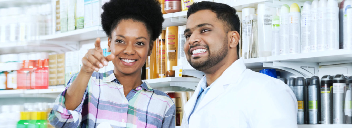 male pharmacist with her customer smiling